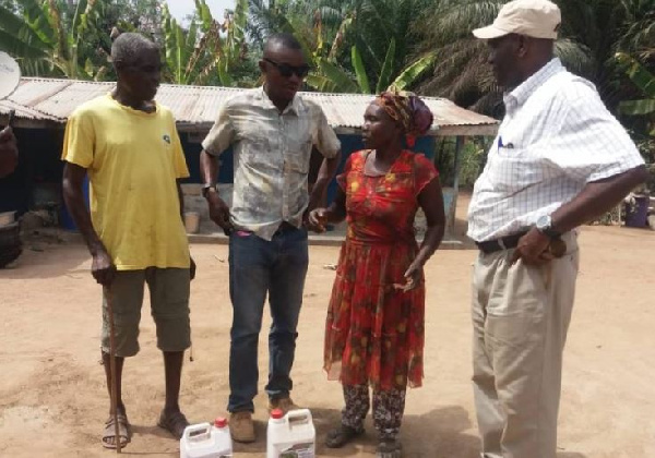 The Commercial Director of New Okaff Industries Limited, Mr. Kwasi Boamah with some farmers affected