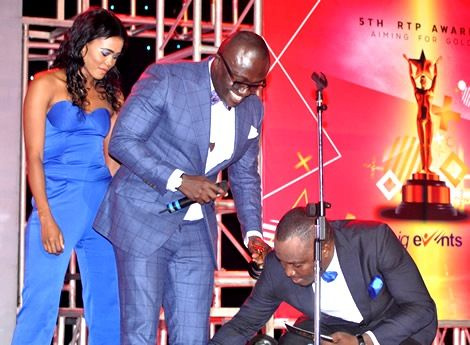 DKB cleans Bola Ray's shoes