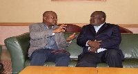 Togbe Afede with an official of the Zimbabwean government