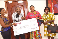 First Lady, Rebecca Akufo-Addo takes a check of GHC10,000 from KFC management.