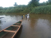 Some pupils crossing the Densu River to school