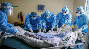 Medical team rolls a coronavirus patient from a bed onto a stretcher