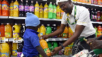 A supermarket attendant gives a bottle of juice to a child shopping with his parents in Nairobi