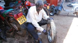 Lwanga repairs a motorcycle tyre. He has been repairing motorcycles since 1957