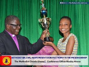 One of the students presenting the trophy to the Bishop