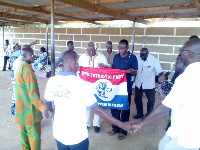 Rex Asanga (right) and Prof. Abole (left) hold the party's flag as supporters pray for victory