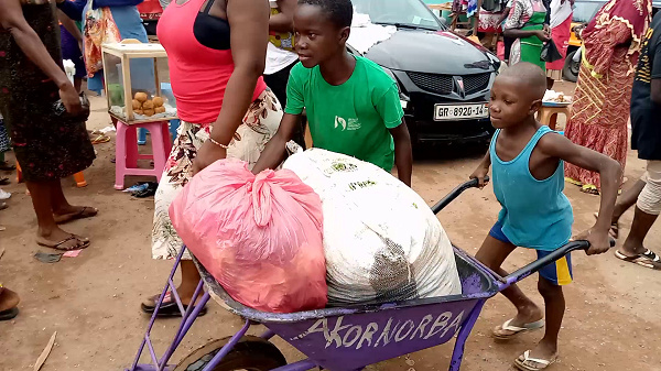 An image of a child pushing a load at the Agomanya market