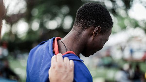 A person shows a scar on his neck as he takes refuge outside a local park near the Sydenham Police