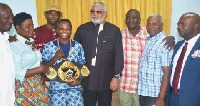 Ex-Prez Rawlings (in black) poses with Isaac Dogboe. Looking on are officials of GBA
