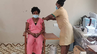 A health personnel administering COVID-19 vaccine to a woman