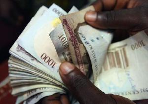 File photo of a man counting naira notes