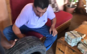 One of the suspects taking the money out of a lorry tyre
