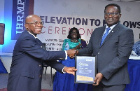John Wilson (right) receiving his citation as Fellow from John Mbroh