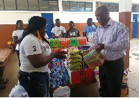Mr. Freddie Tetteh of the school receiving the donated items from Madam Herty Corgie