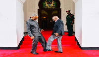 President John Magufuli (R) exchanging a foot greeting with opposition politician
