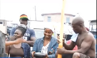 Yeboah pounding the fufu with some neighbours looking on