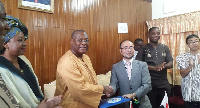 Alex Segbefia exchanging the documents with Koji Makino