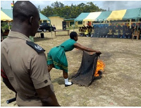 A student carrying out a demonstration on dousing fire