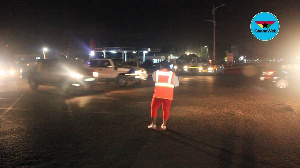 Mrs. Margaret Ansah using the flashlight from her phone to direct traffic at Madina Ritz junction
