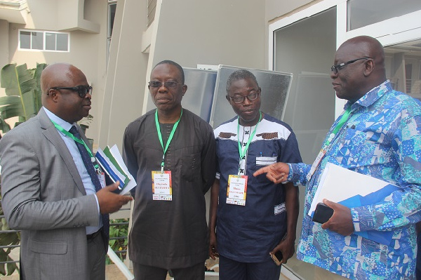 Dr. Emmanuel Agyemang Dwomoh (extreme left) interacting with some participants after the forum