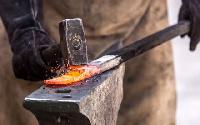 Blacksmith works on red hot iron.     File photo.