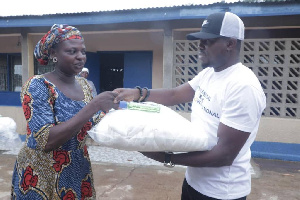 Management of Essential Relief International presenting adult diapers to a beneficiary