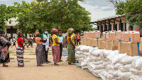 Women await in line during an United Nations World Food Program's distribution