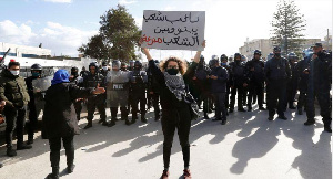 A demonstrator holds up a sign during an anti-government protest in Tunis, (REUTERS/Zoubeir Souissi)