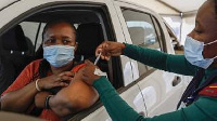 A woman receives a dose of the Johnson and Johnson Covid-19 vaccine from a healthcare worker