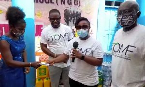 Edith Obeng Hammand (middle) presents a cheque to the founder of the Orphanage