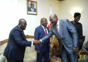 President Akufo-Addo in a handshake with Mr Mahama with others in the background