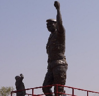 Former President Jerry John Rawlings standing before the statue of  Thomas Sankara