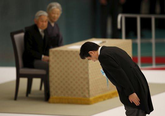 Japan's Prime Minister Shinzo Abe (R) bows in front of Japan's Emperor Akihito (L)
