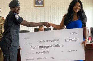 Yvonne Okoro presenting $10,000 to Black Queens