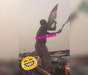 The man is spotted with two NDC flags standing on a taxi