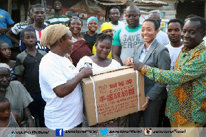 Dr. Zanetor Agyeman-Rawlings presenting a machine to one of the beneficiaries