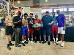 Dogboe holding his belt surrounded by his team at the gym