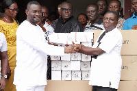 John Kumah presenting street lighting bulbs to the  Presiding Member of the assembly Michael Owusu