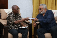 Samuel Ntim Darkwa presenting the book to former President Jerry John Rawlings
