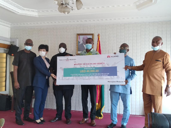Huawei officials presenting a dummy cheque to deputy Sports Minister (second right)