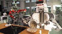 A robot pours popcorn from a cooking pot into a bowl at Bremen University, Northwestern Germany