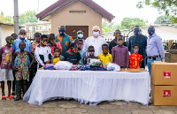 Fr Andrew Campbell  receiving items from  MASK4ALL Ghana