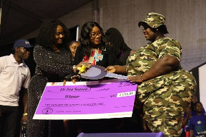 Winner of Di Asa season 3, Precious Mensah [R] receiving a dummy cheque at the grand finale