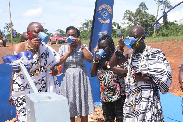 Community leaders of Freboye drinking water from the borehole after the sod cutting ceremony