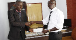 General-Secretary of Opticians Association of Ghana, Frank Ofori  presenting a cheque to Mr Boakye