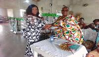Mrs. Akasi Hormah-Miezah, treasurer of NPP in the Western Region presents cash to Basake community