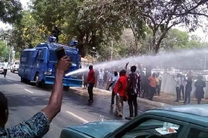Water cannons containing hot chemical solution being used on protestors