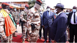 Colonel Mamady Doumbouya, left, greets Ivory Coast's President Alassane Ouattara, right