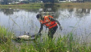 Body of the deceased being retrieved from the pond by an official of NADMO
