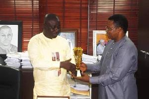 Isaac Adongo receiving the plaque